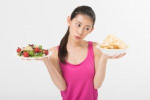バランスの良い食事とお菓子を天秤にかける女性