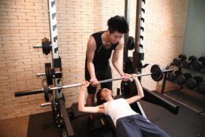 男性がトレーニングする女性の補助をしている